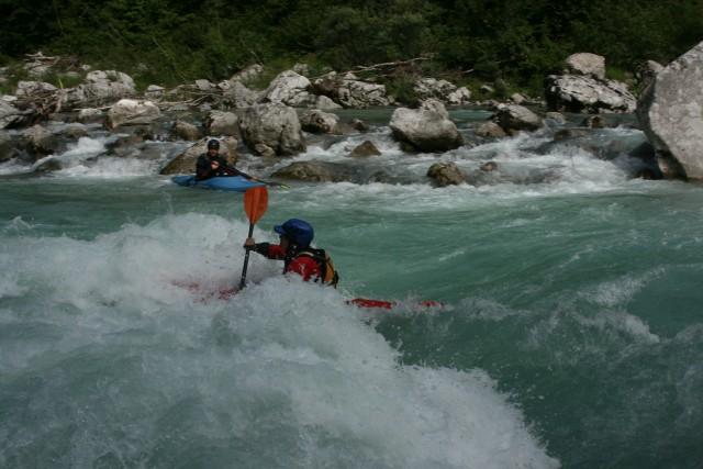 Kajak fährt durch eine schäumende Welle.