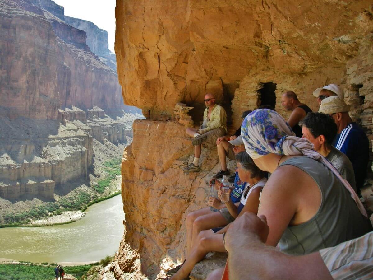 Menschen sitzen an Felswand, unter ihnen der Colorado River