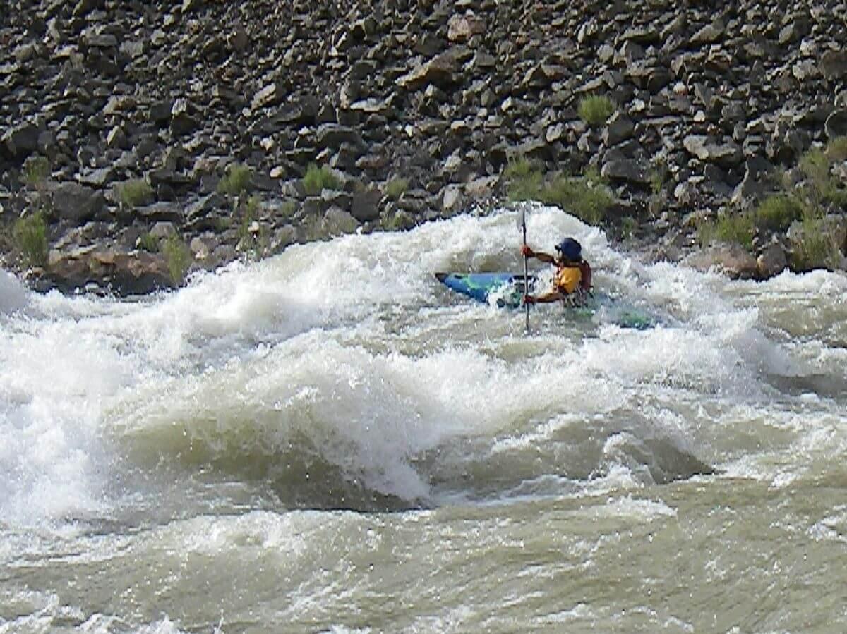 Kajak fährt über riesige schäumende Welle