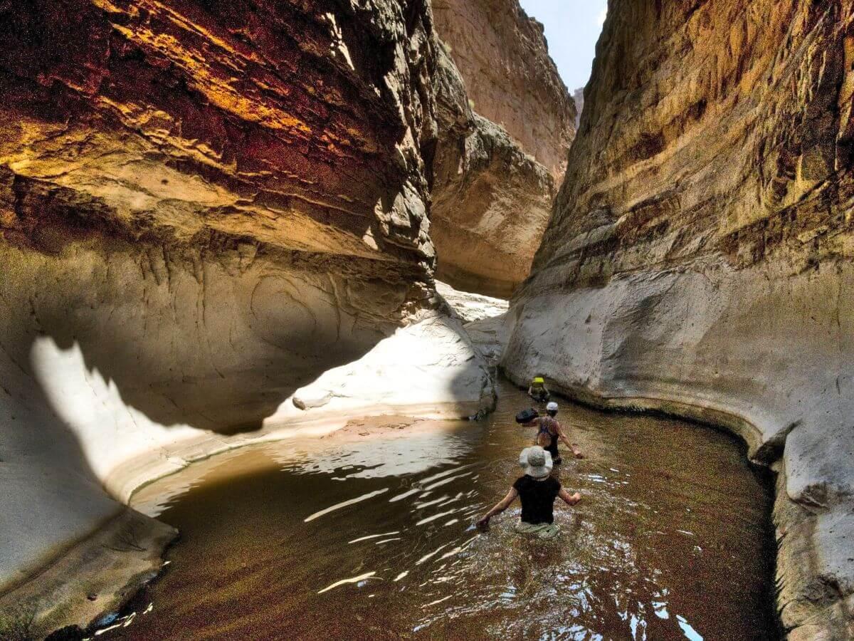 Menschen waten durch hüfttiefes Wasser in einem Felskessel