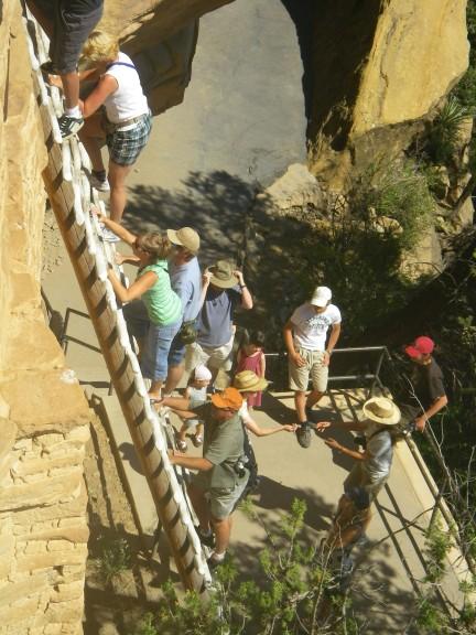Touristen klettern eine hohe Leiter hinauf.