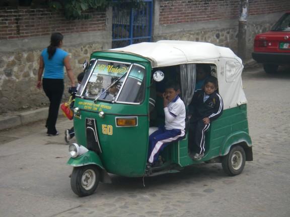 Dreirad-Taxi mit Schulkindern.