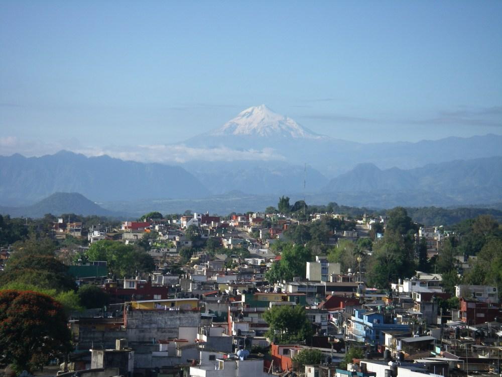 Hinter der Stadt ragt der Vulkan in den Himmel.