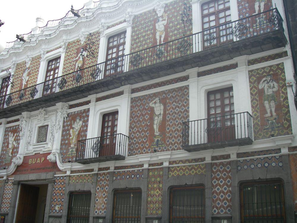 Haus mit braunen Kacheln und eisernen Balkongittern.
