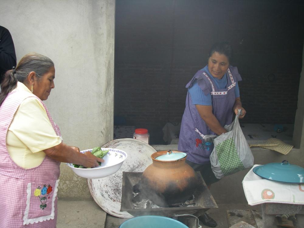 Zwei Frauen kochen im Hof eines Hauses.
