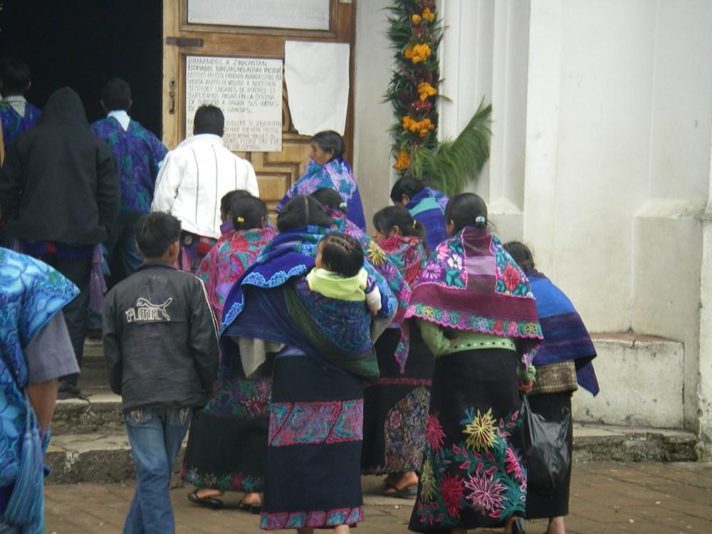 Frauen mit bunten Schultertüchern gehen in die Kirche.