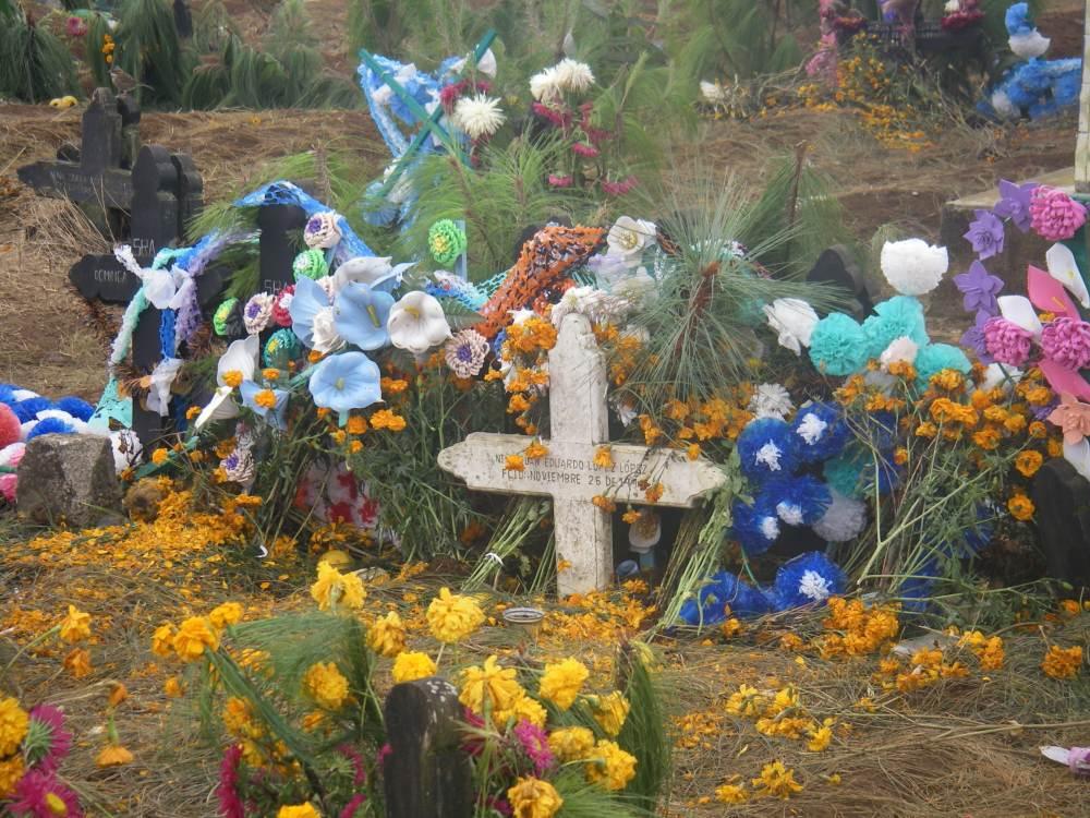 Grabkreuz umgeben von bunten Blumen.