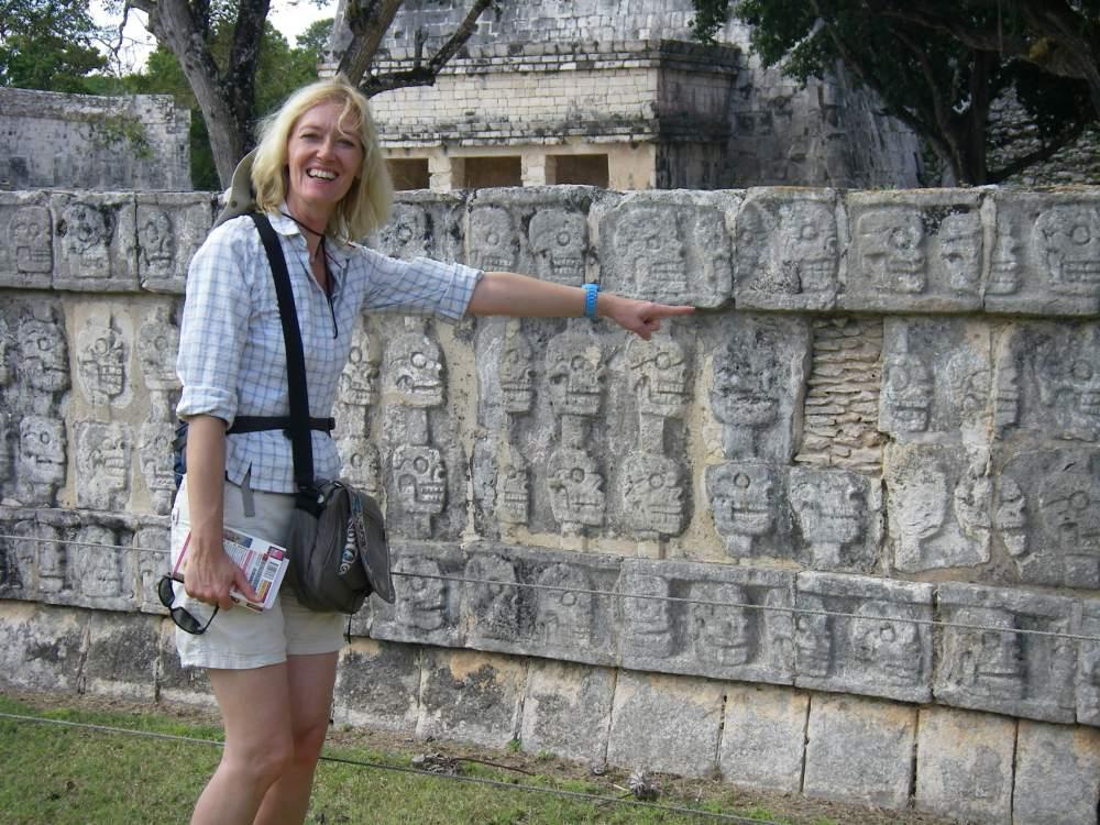 Gina zeigt auf Altar mit Totenköpfen.