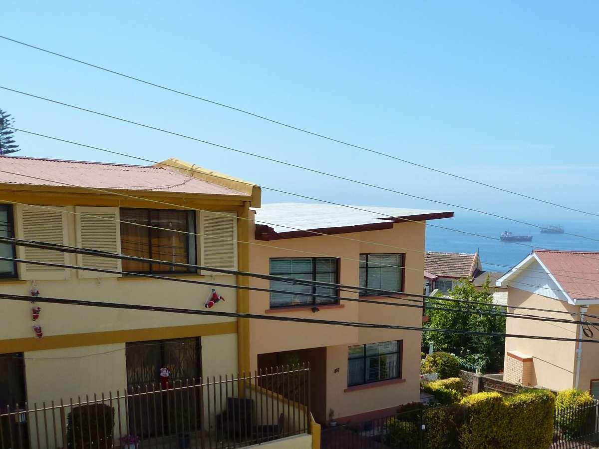 flache Häuser mit Kletternikoläusen, dahinter das Meer