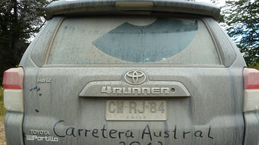 """Staubbedeckter Geländewagen mit """"Carretera Austral"""" in den Staub geschrieben."""
