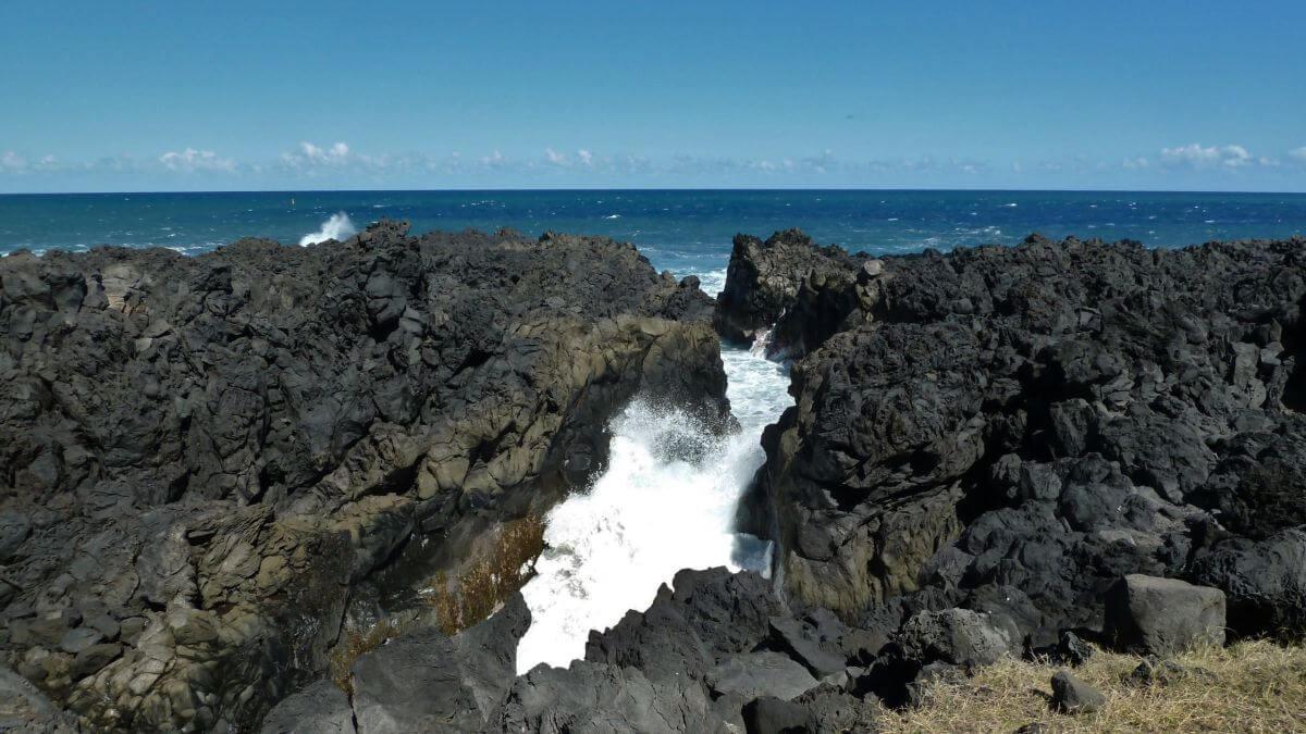 Meerwasser schäumt in schmaler Felsspalte.