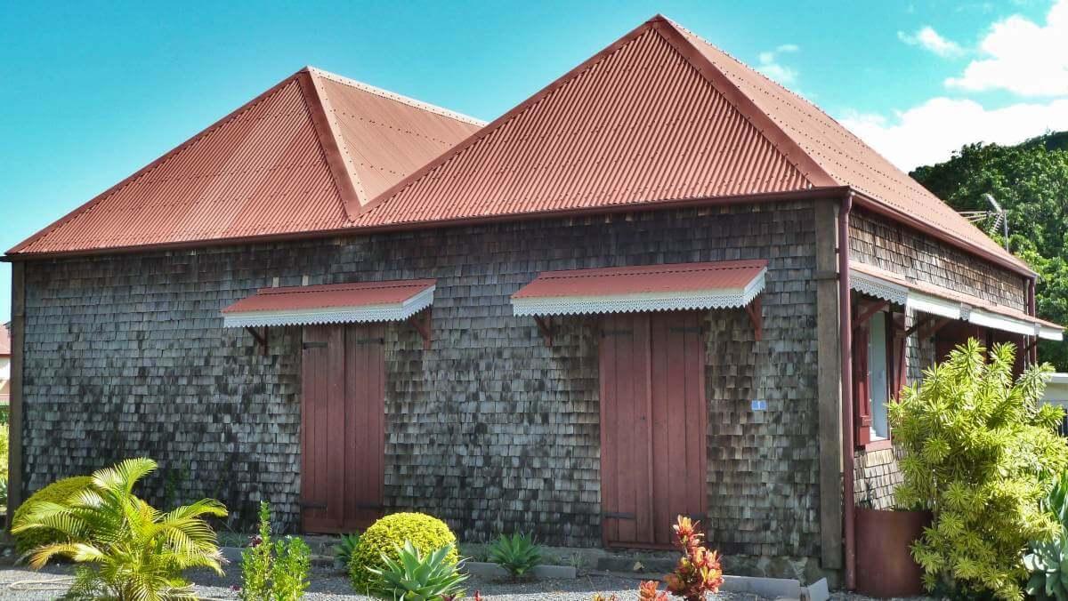 Haus mit Holzschindelwänden und kleinen Vordächern.