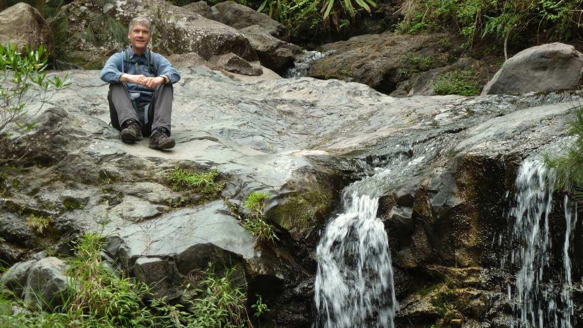 Marcus sitzt auf einem Felsplateau neben einem kleinen Wasserfall.