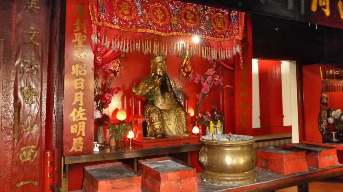 Roter Schrein mit goldener Buddhafigur.