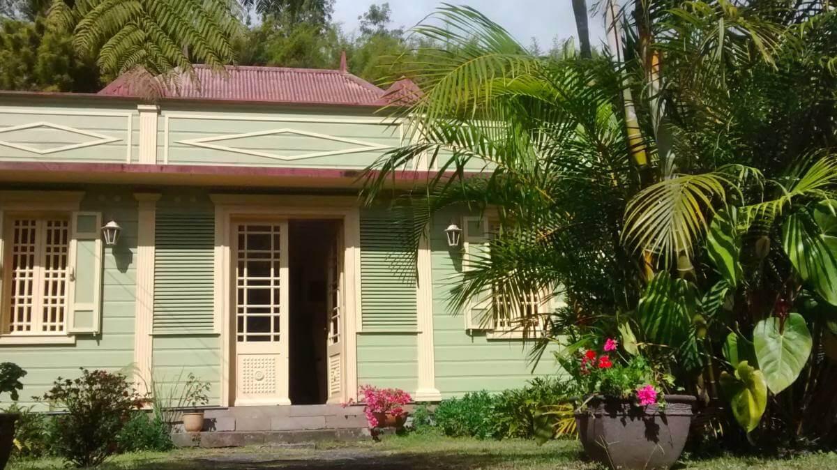Hellgrünes Holzhaus mit Veranda.