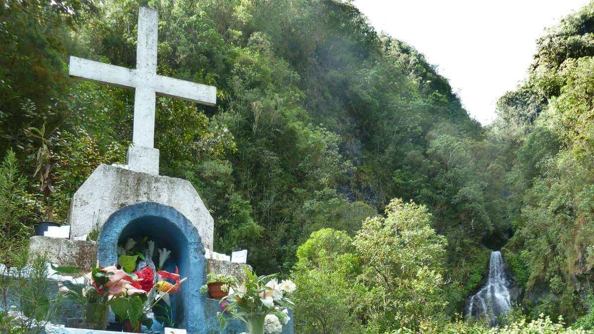 Weißer Schrein mit Kreuz im Wald.