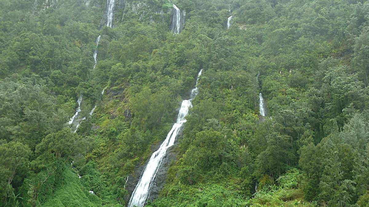 Grüner Berghang mit vielen Wasserfällen.