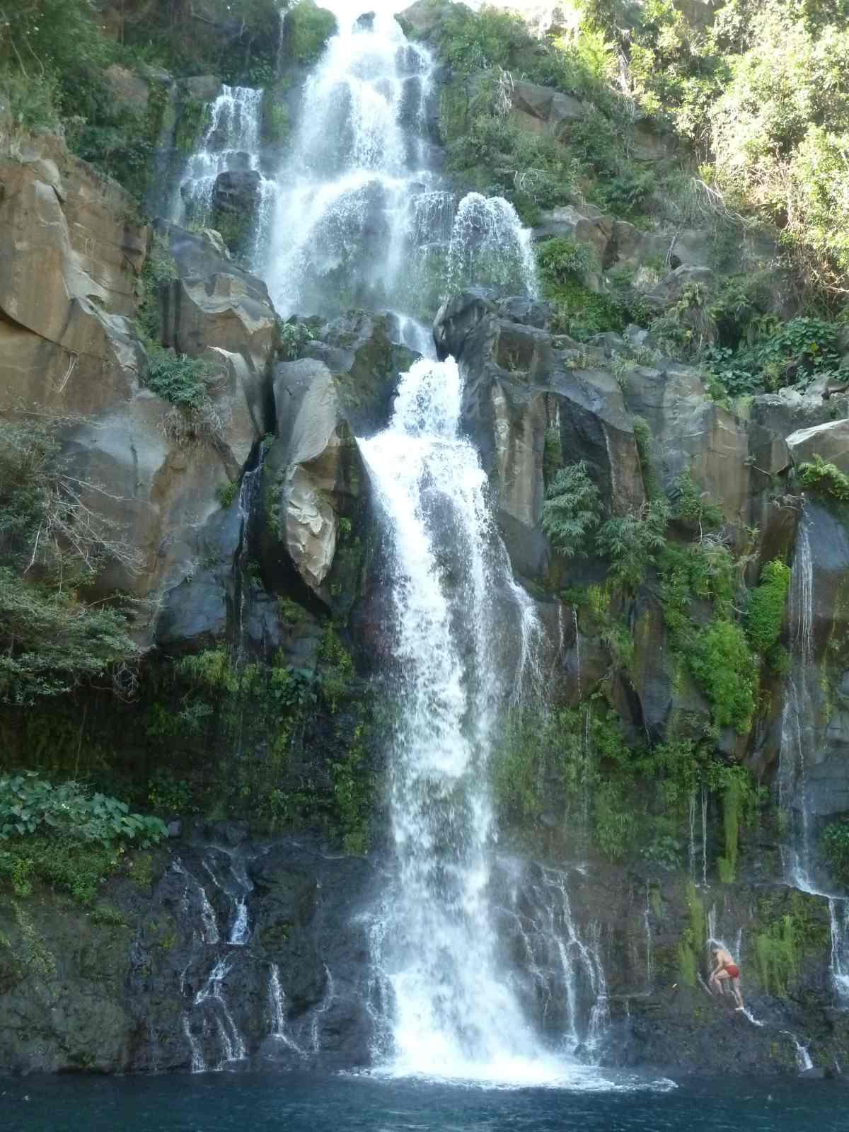 Wasserfall stürzt an einer Felswand runter.
