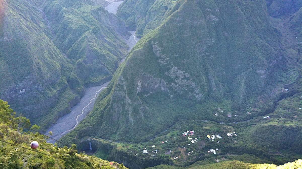 Tiefes Tal mit ein paar Häusern im Talgrund.