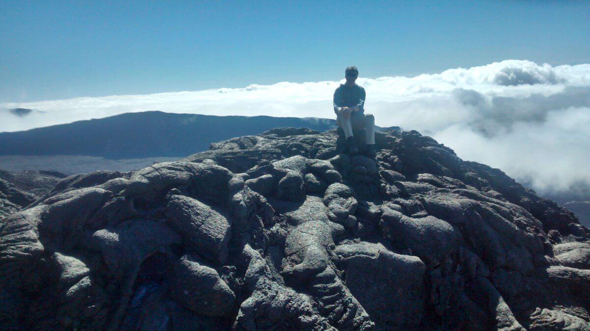 Marcus sitzt auf dem Lavagestein des Vulkans auf La Reunion.