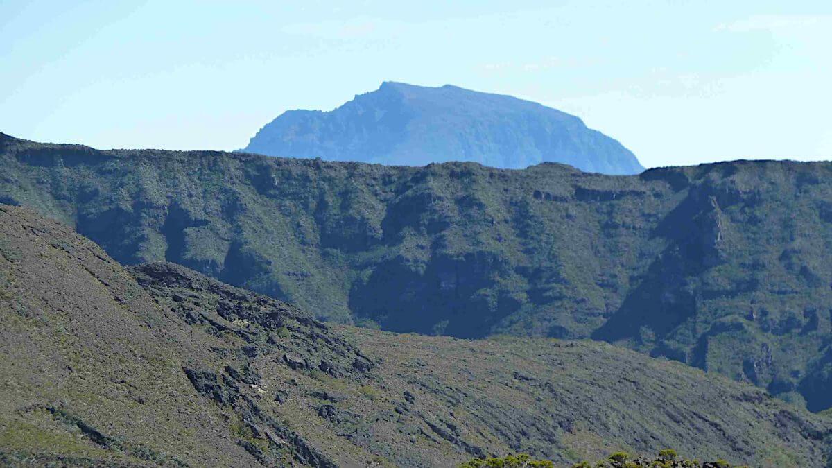 Hinter dem Bergrücken erhebt sich in der Ferne der abgerundete Gipfel des Pitons des Neiges.