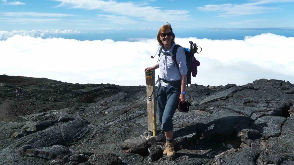 Gina steht am Wegweiser zum Gipfel des Piton de la Fournaise.