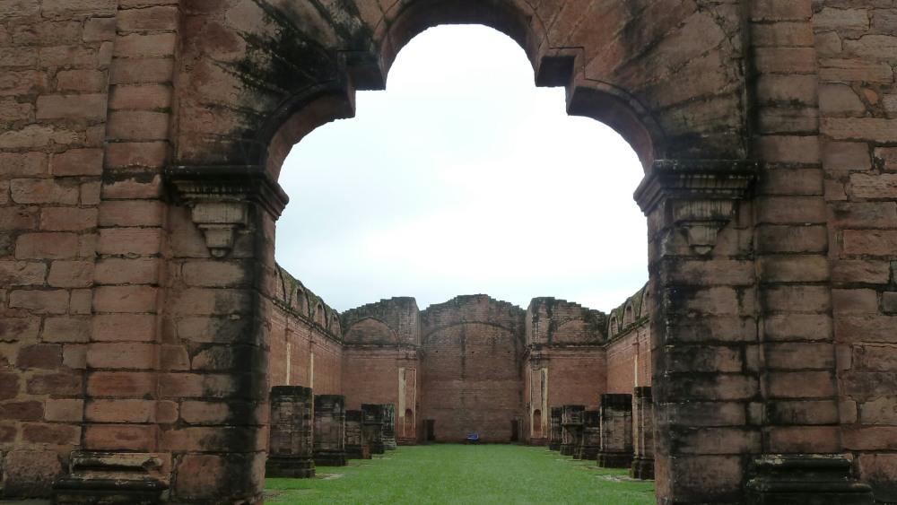Blick durch einen gewölbten Bogen auf die Mauern der Kirche.