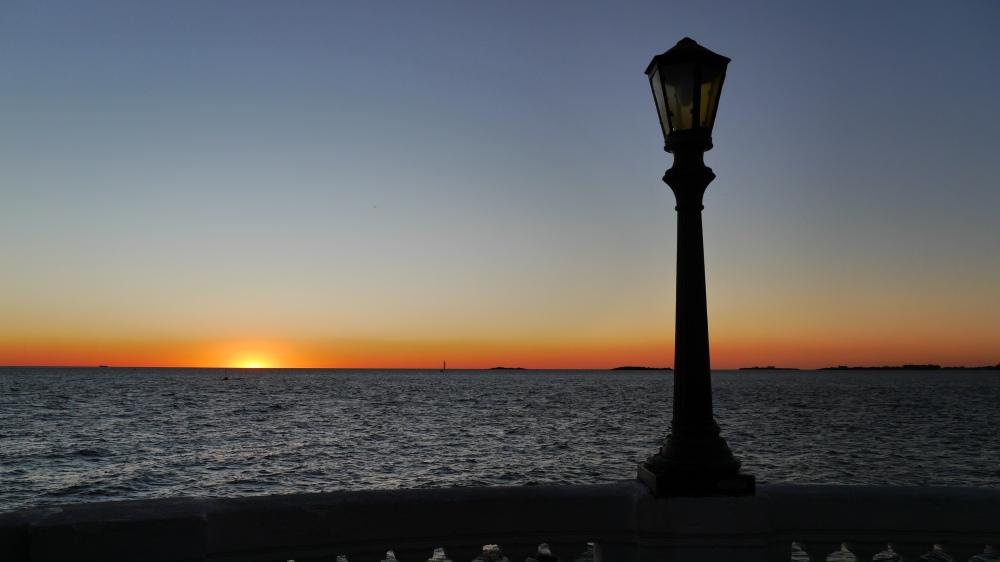 Silhouette einer Straßenlaterne vorm Sonnenuntergangs-Himmel.