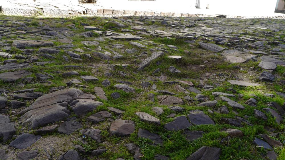 Sehr unregelmäßiges Steinpflaster mit Gras dazwischen.