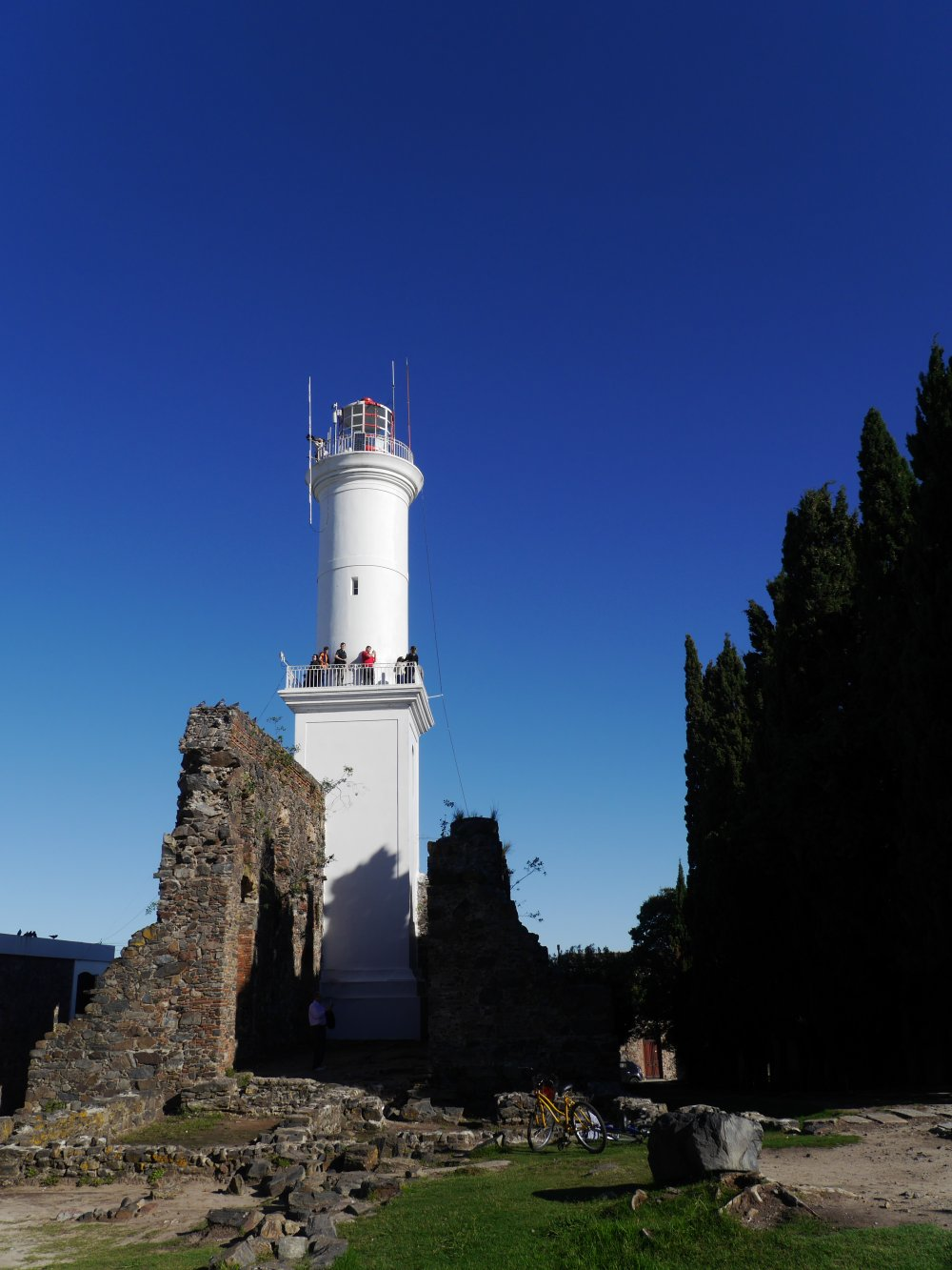 Weißer Leuchtturm vor blauem Himmel.