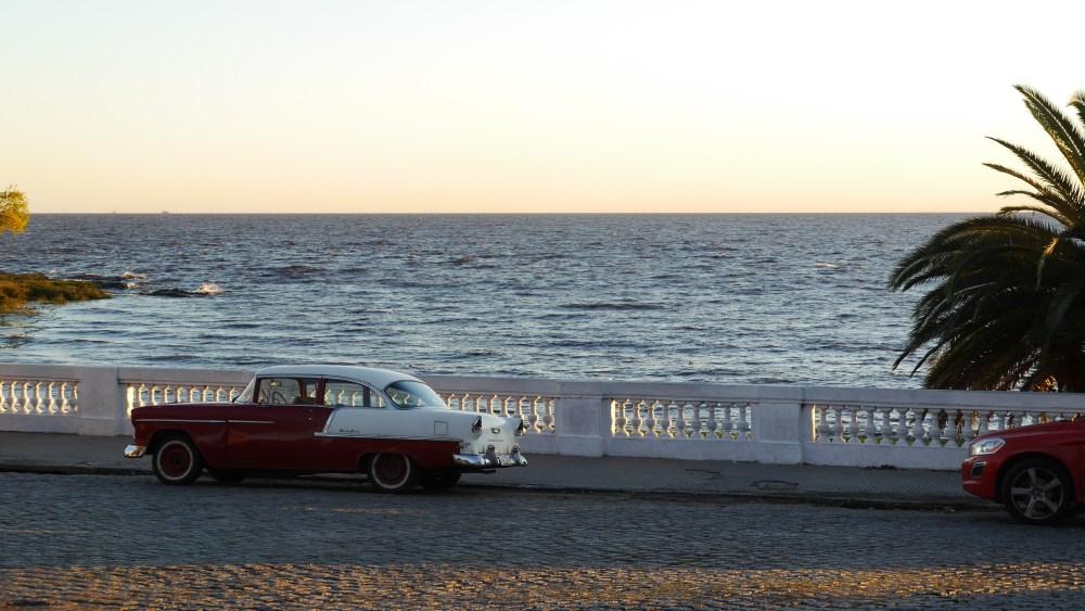 Uferstraße mit Steingeländer, ein rot-weißer Oldtimer parkt davor.