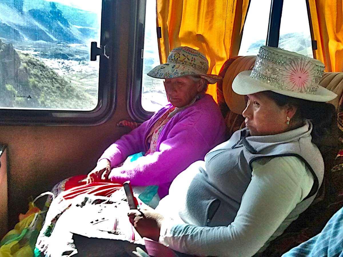 Zwei Frauen mit indigener Tracht und Handy in der Hand sitzen im Bus.