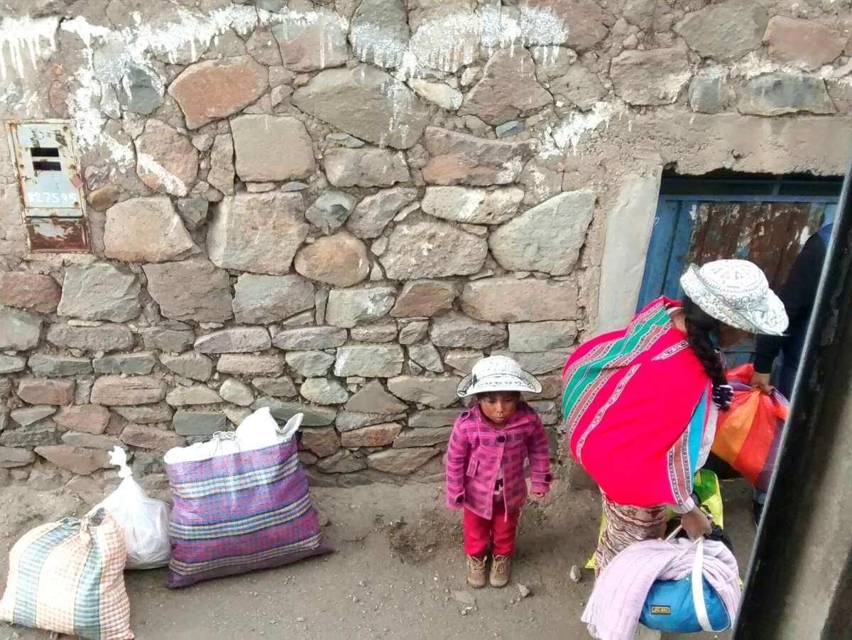 Indigene Frau mit kleinem Kind und vielen Taschen steht neben dem Bus zum Colca Canyon.