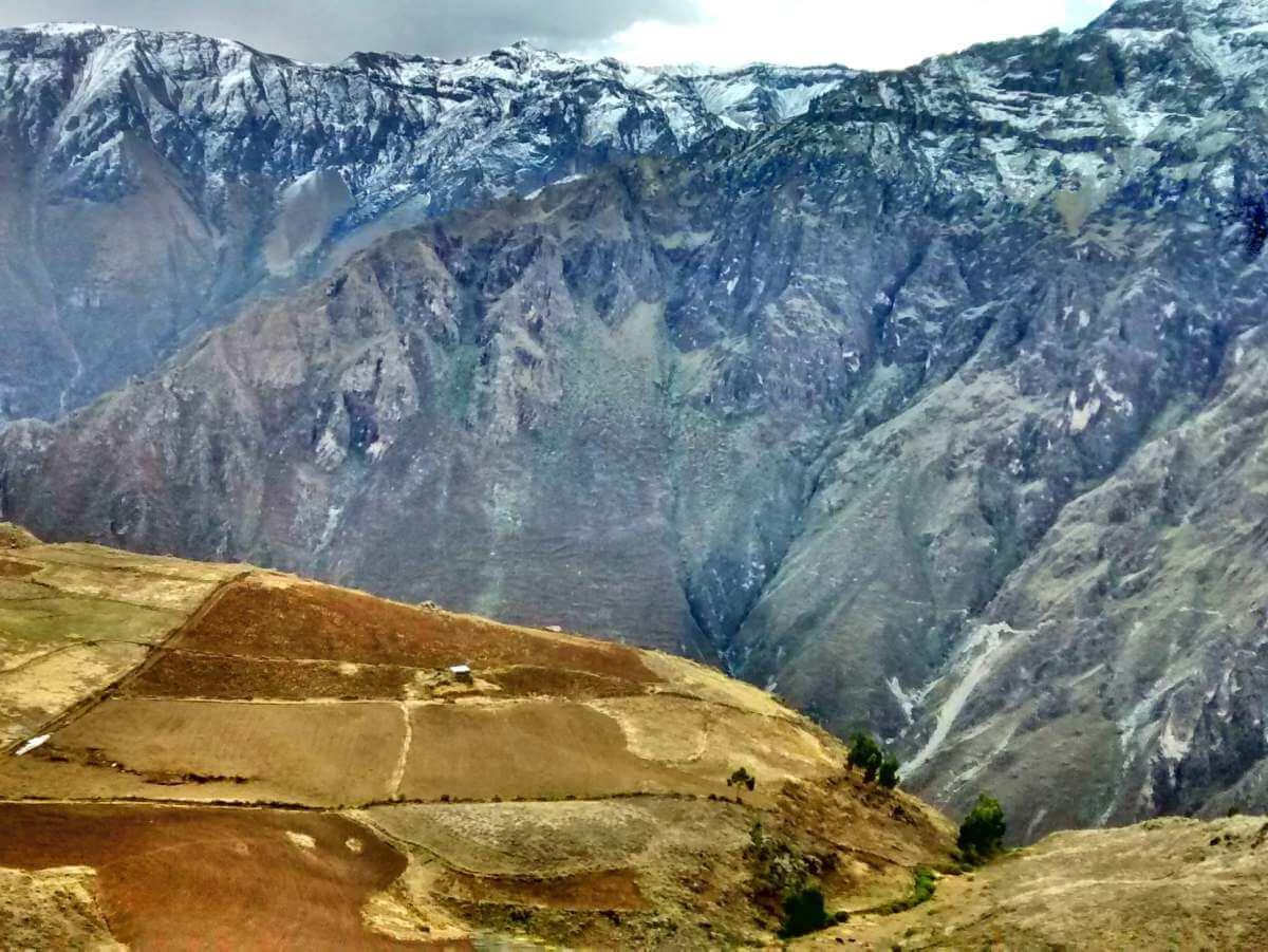 Plateau mit Feldern, dahinter steile Felswände des Colca Canyon.