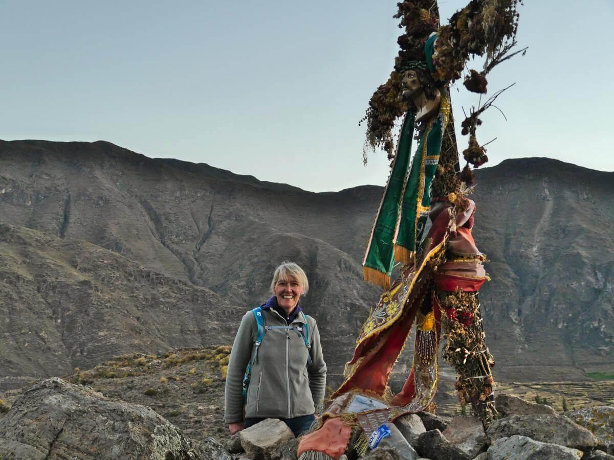 Gina steht vor einem bunt geschmückten Gipfelkreuz im Abendlicht.
