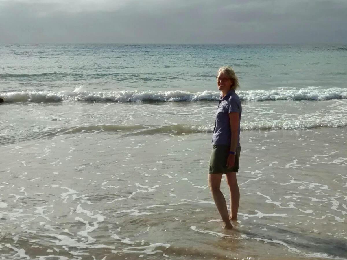 Gina steht im flachen Wasser des Anakena Strandes der Osterinsel.