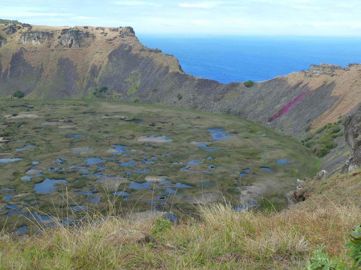 Mit Wasserlachen bedeckter Krater, dahinter der Pazifik.