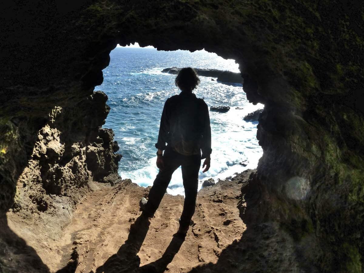 Marcus steht in der Öffnung der Höhle zum Meer.
