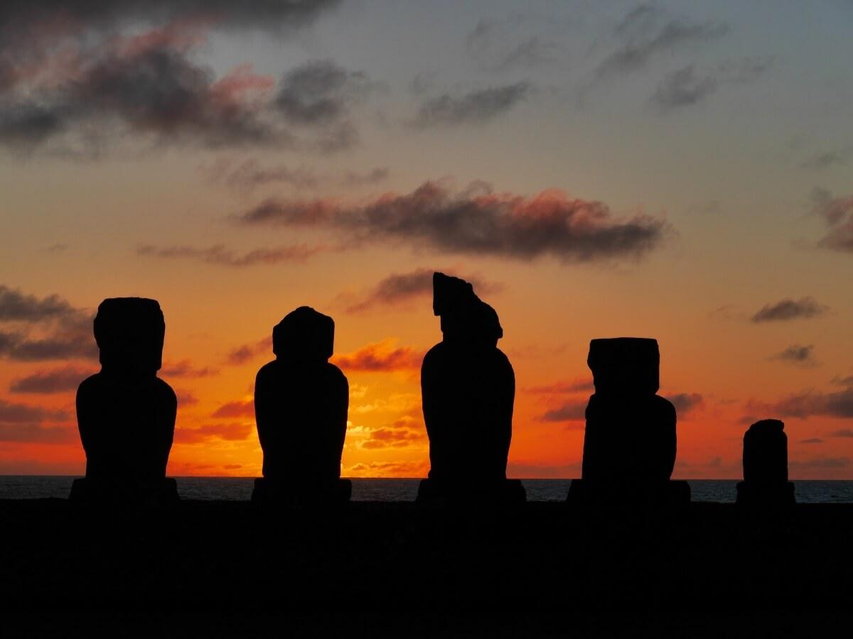 Fünf Figuren von Moai im Licht des Sonnenuntergangs.