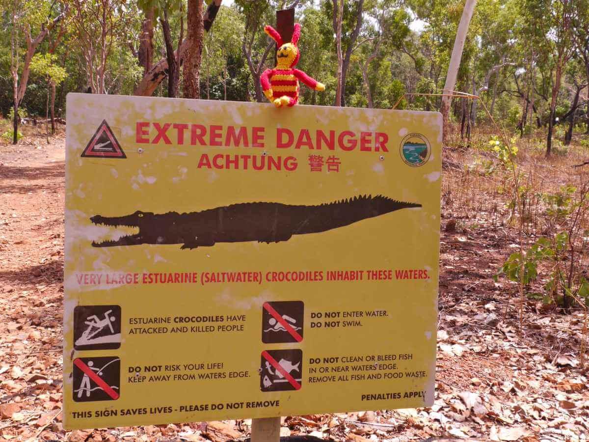 Reise-Ringel auf einem Krokodil-Warnschild.