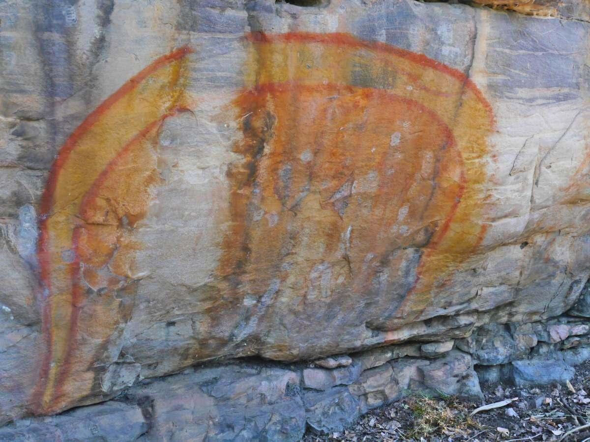 Felszeichnung einer orangenen Schlange.
