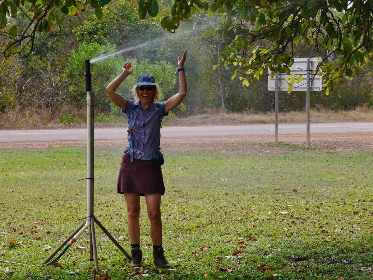 Gina steht unterm Rasensprenger.
