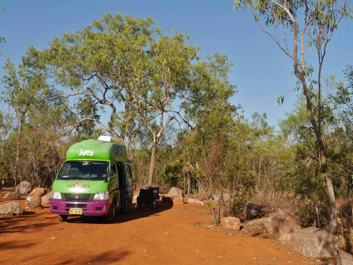 Grüner Campervan steht auf Platz mit roter Erde.