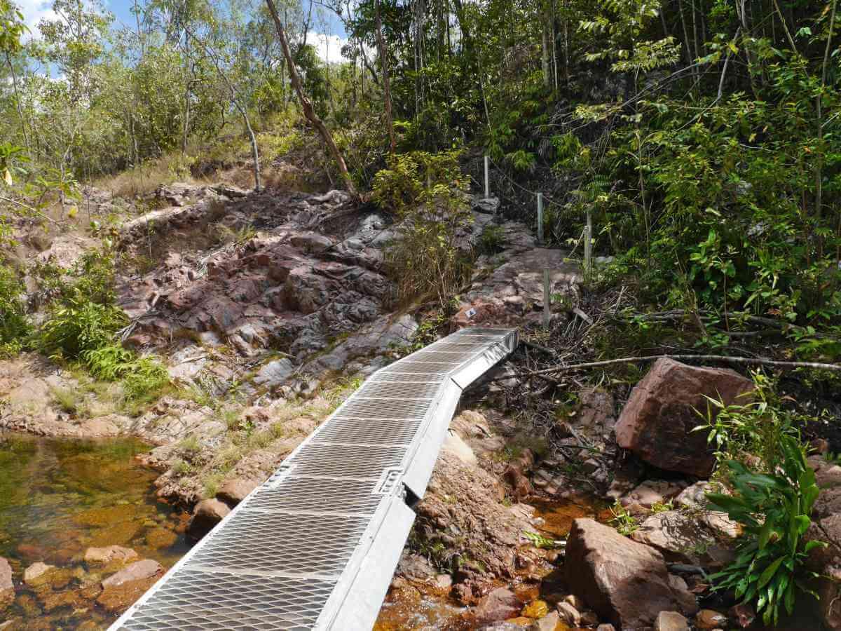 Steg aus Metallgitterplatten führt über steiniges Bachbett.