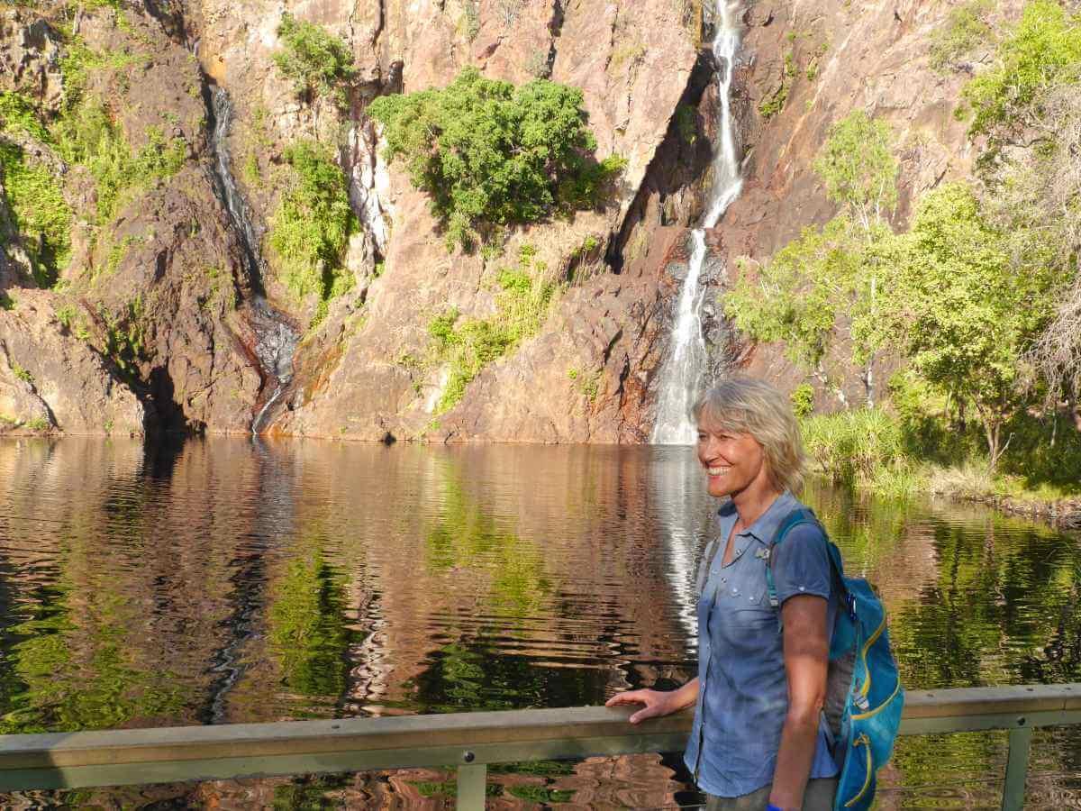 Gina steht vor einem kleinen See, im Hintergrund kommt ein schmaler Wasserfall die Felswand herunter.