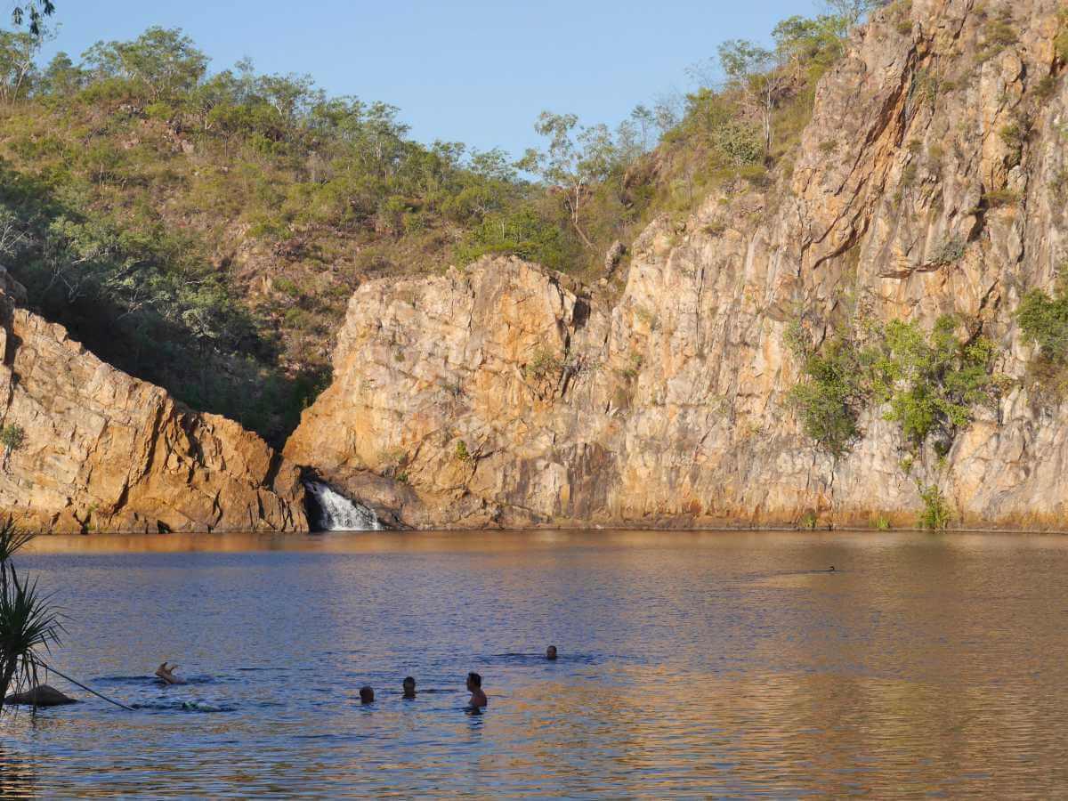 Schwimmer im See vor Felskulisse und Wasserfall.
