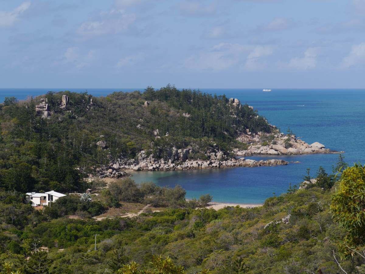 Blick auf grüne Hügel und eine Bucht am Meer.