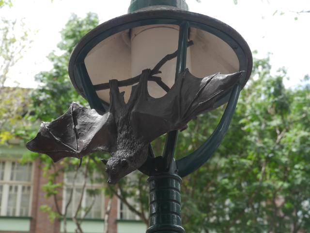 Fledermaus-Skulptur an einer Laterne.