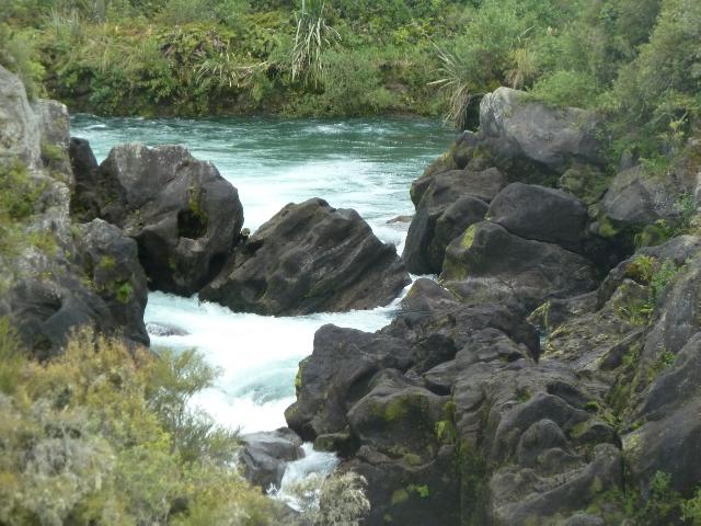Dunkle Felsblöcke werden vom Wasser umpült.