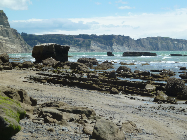 Felsiger Strand und viele weiße Schaumkronen auf dem Meer.